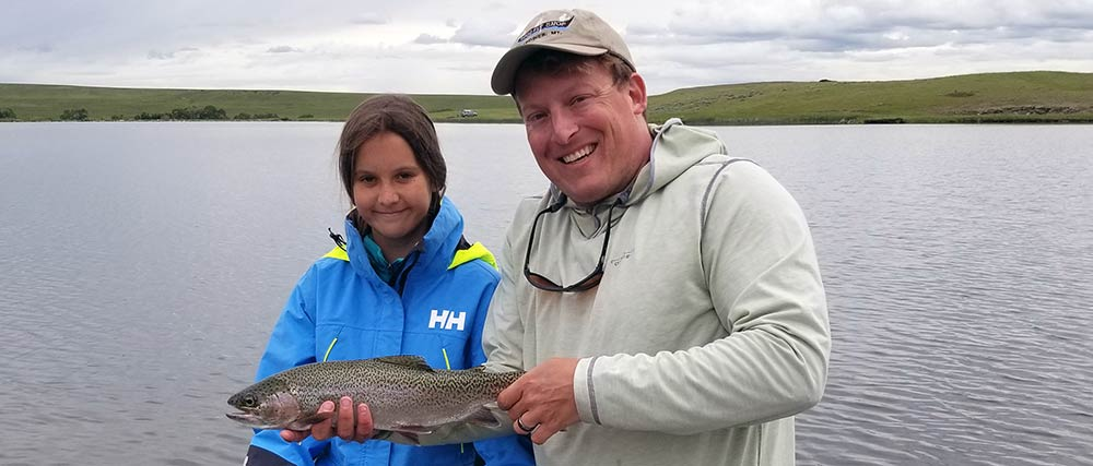 young woman, montana fishing guide, and large rainbow trout on montana private water fishing trip